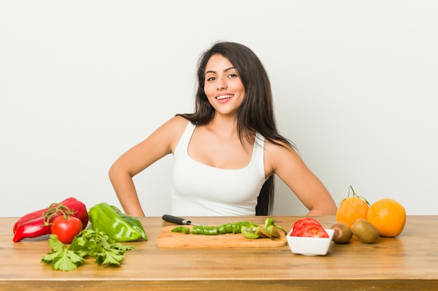 Young curvy woman preparing a healthy meal confident keeping hands on hips.
