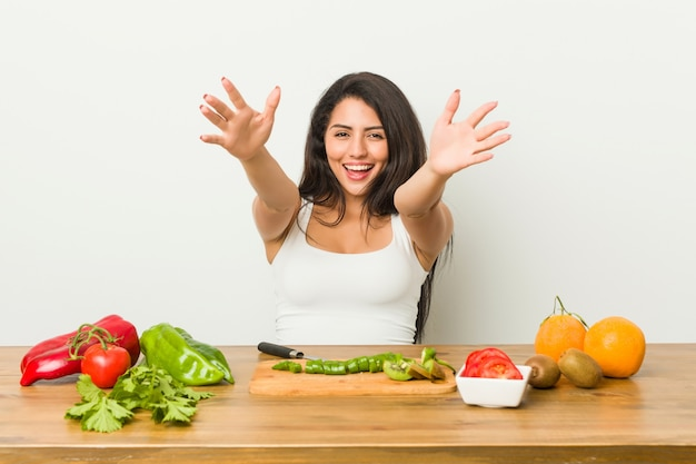 Young curvy woman preparing a healthy meal feels confident giving a hug to the camera.