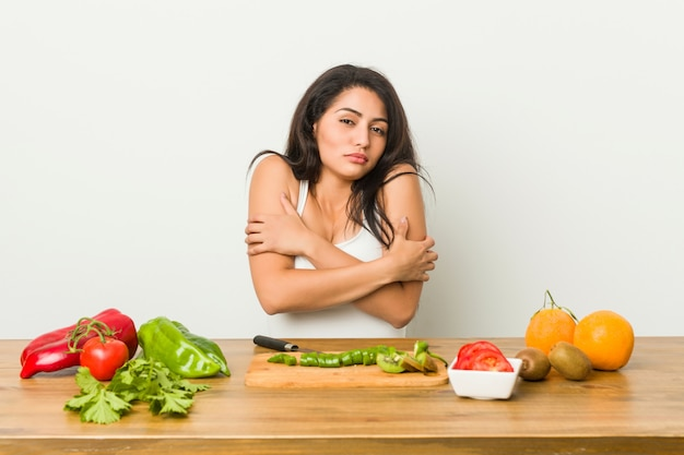 Young curvy woman preparing a healthy meal going cold due to low temperature