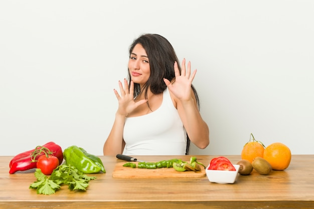 Young curvy woman preparing a healthy meal rejecting someone showing a gesture of disgust.