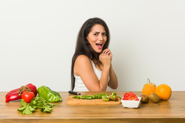 Young curvy woman preparing a healthy meal scared and afraid.