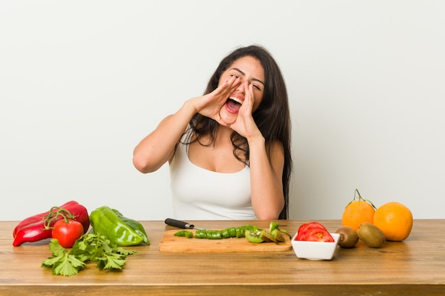 Young curvy woman preparing a healthy meal shouting excited to front.
