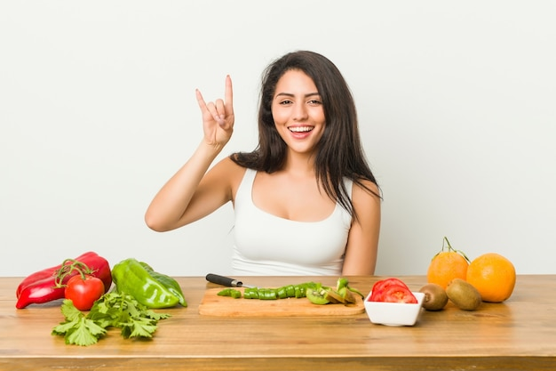 Young curvy woman preparing a healthy meal showing a horns gesture as a revolution concept.