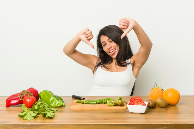 Young curvy woman preparing a healthy meal showing thumb down and expressing dislike.