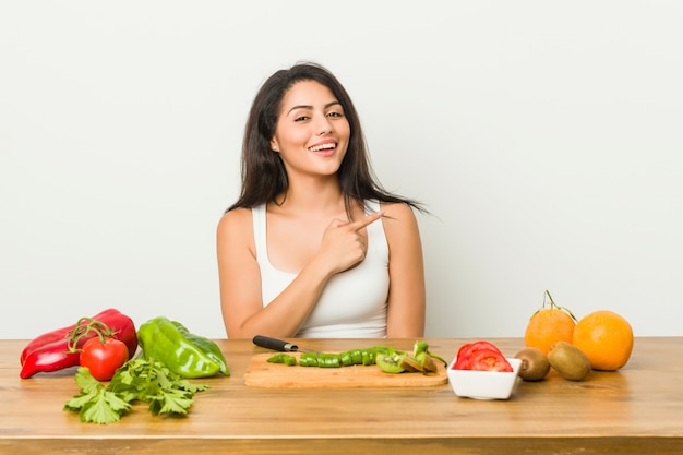 Young curvy woman preparing a healthy meal smiling and pointing aside, showing something at blank space.