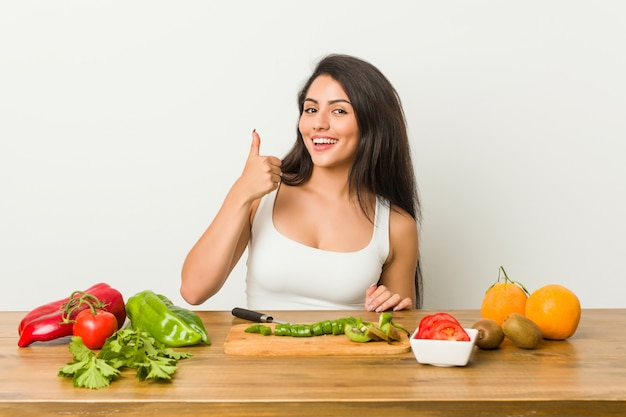 Young curvy woman preparing a healthy meal smiling and raising thumb up