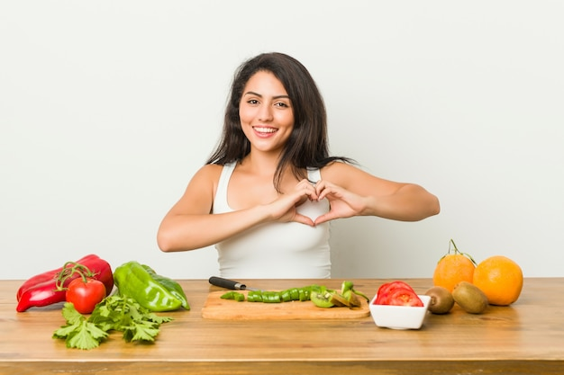 Young curvy woman preparing a healthy meal smiling and showing a heart shape with hands.
