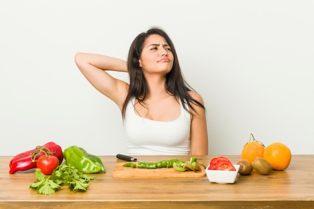 Young curvy woman preparing a healthy meal touching back of head, thinking and making a choice.