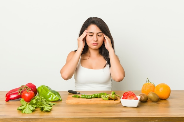 Young curvy woman preparing a healthy meal touching temples and having headache.