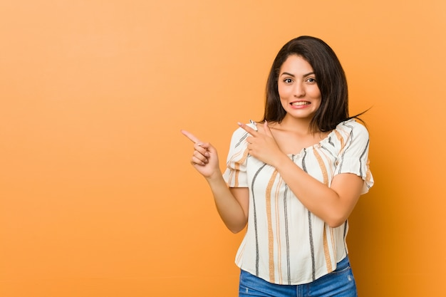 Young curvy woman shocked pointing with index fingers to a .
