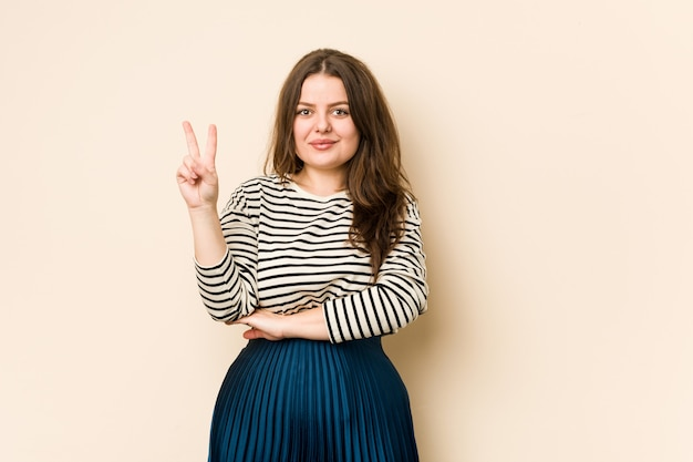 Young curvy woman showing number two with fingers.