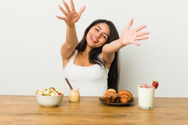 朝食を取って曲線美の若い女性は抱擁を与えることに自信を持っています
