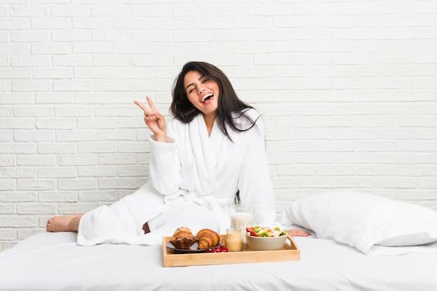 指で平和のシンボルを示す楽しくてのんきなベッドで朝食をとる若い曲線美の女性。