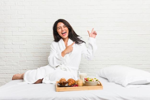 興奮と欲望を表現し、コピースペースに人差し指で指しているベッドで朝食をとっている若い曲線美の女性。