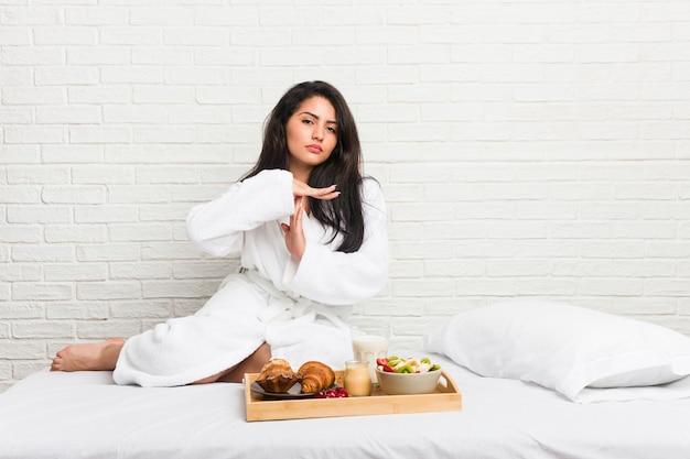 タイムアウトジェスチャーを示すベッドで朝食を取る若い曲線美の女性。