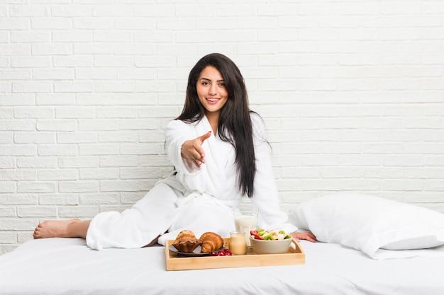 挨拶のジェスチャーでカメラに手を伸ばしてベッドで朝食を取る若い曲線美の女性。