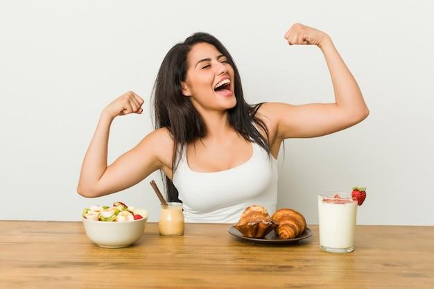 勝利、勝者の概念の後に拳を上げる朝食を取る若い曲線美の女性。