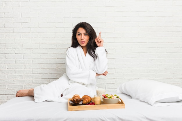 Young curvy woman taking a breakfast on the bed having some great idea,  of creativity.