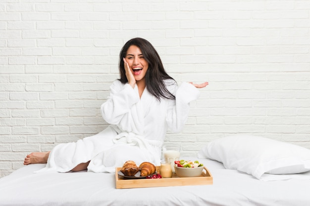 Young curvy woman taking a breakfast on the bed holds  on a palm, keep hand over cheek. amazed and delighted.