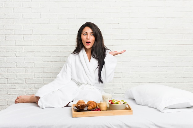 Young curvy woman taking a breakfast on the bed impressed holding copy space on palm.