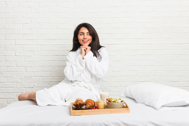 Young curvy woman taking a breakfast on the bed keeps hands under chin, is looking happily aside.