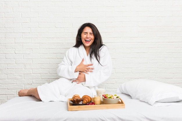 Young curvy woman taking a breakfast on the bed laughs happily and has fun keeping hands on stomach.