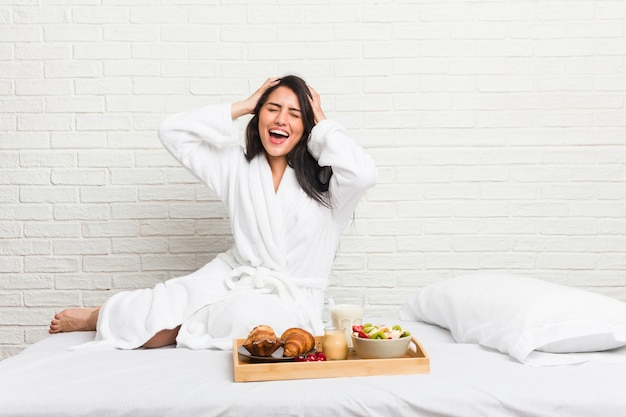 Young curvy woman taking a breakfast on the bed laughs joyfully keeping hands on head