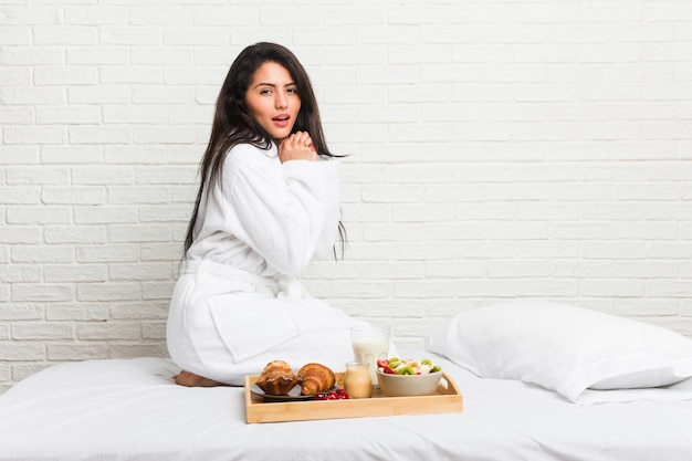 Young curvy woman taking a breakfast on the bed scared and afraid.