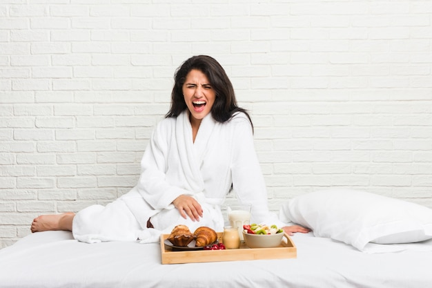 Young curvy woman taking a breakfast on the bed screaming very angry and aggressive