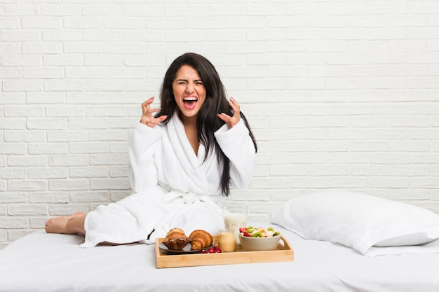Young curvy woman taking a breakfast on the bed screaming with rage.