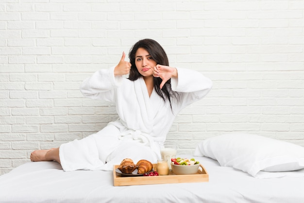 Young curvy woman taking a breakfast on the bed showing thumbs up and thumbs down