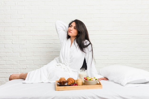 Young curvy woman taking a breakfast on the bed touching back of head, thinking and making a choice.