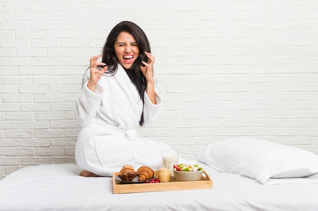 Young curvy woman taking a breakfast on the bed upset screaming with tense hands.