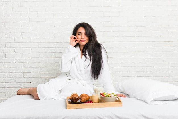 Young curvy woman taking a breakfast on the bed with fingers on lips keeping a secret.