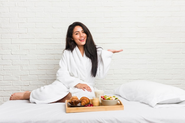 Young curvy woman taking a breakfast on the bed
