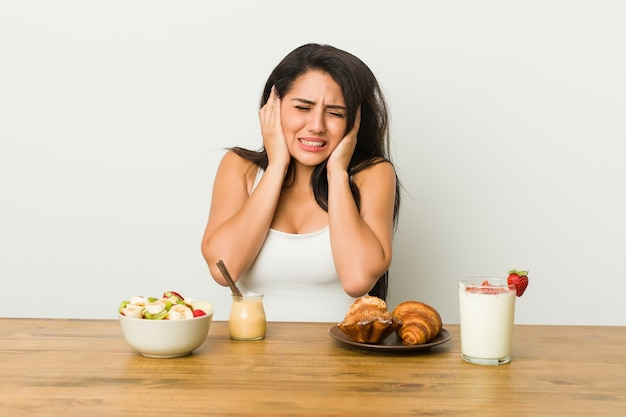 Young curvy woman taking a breakfast covering ears with hands.