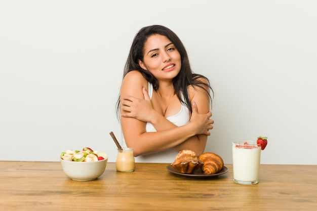 Young curvy woman taking a breakfast going cold due to low temperature or a sickness.