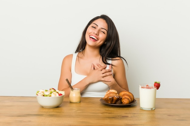 Young curvy woman taking a breakfast has friendly expression, pressing palm to chest. love concept.