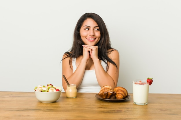 Young curvy woman taking a breakfast keeps hands under chin, is looking happily aside.
