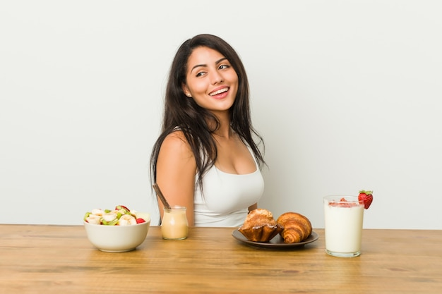 Young curvy woman taking a breakfast looks aside smiling, cheerful and pleasant.