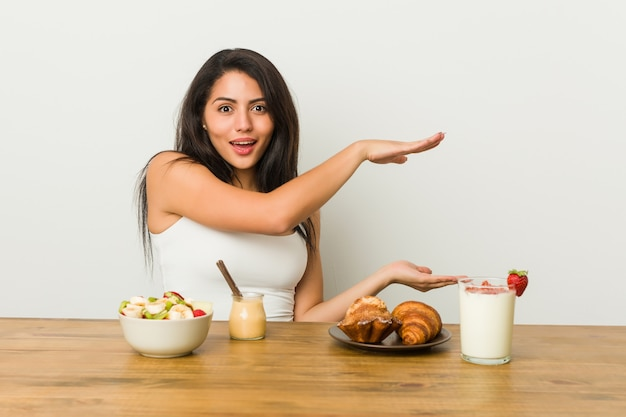 Young curvy woman taking a breakfast shocked and amazed holding a copy space between hands.