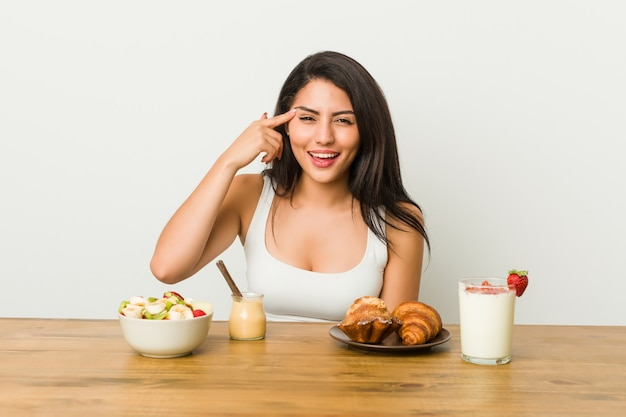 Young curvy woman taking a breakfast showing a disappointment gesture with forefinger.