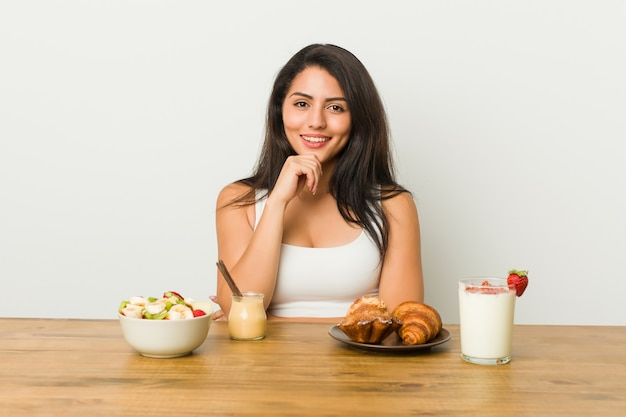 Young curvy woman taking a breakfast smiling happy and confident, touching chin with hand.