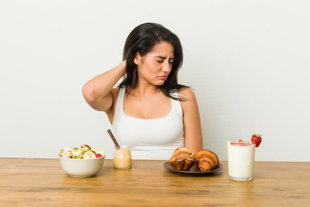 Young curvy woman taking a breakfast suffering neck pain due to sedentary lifestyle.