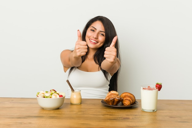 Young curvy woman taking a breakfast with thumbs ups, cheers about something, support and respect concept.