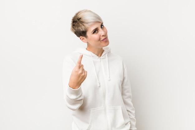 초대하는 것처럼 손가락으로 가리키는 흰색 까마귀를 입고 젊은 매력적인 여자가 더 가까이 오십시오.