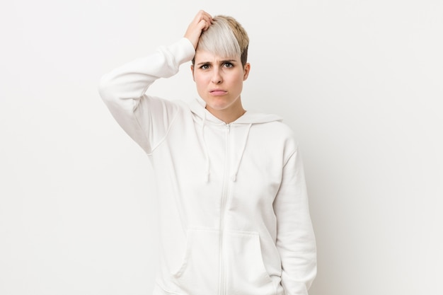 Young curvy woman wearing a white hoodie being shocked, she has remembered important meeting.