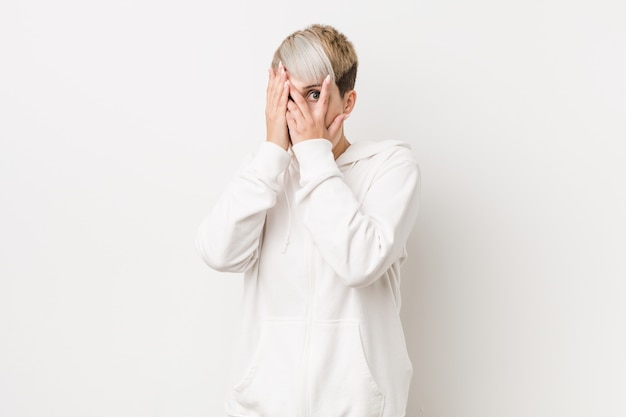 Young curvy woman wearing a white hoodie blink through fingers frightened and nervous.