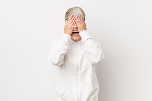 Young curvy woman wearing a white hoodie covers eyes with hands, smiles broadly waiting for a surprise.