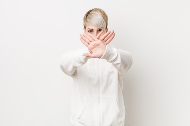 Young curvy woman wearing a white hoodie doing a denial gesture